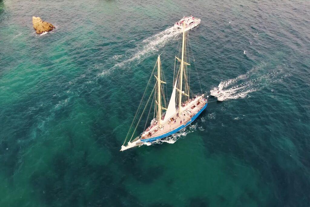 Vuelo de evento deportivo y audiovisual con dron sobre el mar. Evento en un velero grabado con un dron