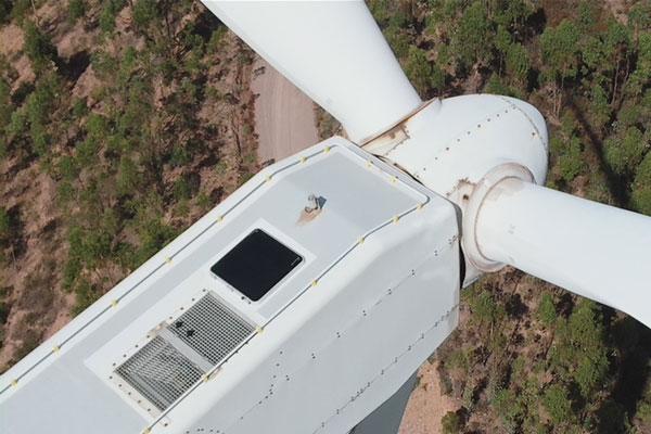 Detalle de la inspección técnica con dron sobre un aerogenerador con la cámara visual, en un parque eólico.